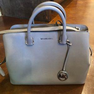 Michael Kors light grey purse with shoulder strap.